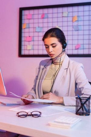 Photo pour Opérateur féminin dans casque regardant les documents dans le bureau - image libre de droit