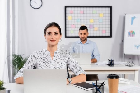 cheerful businesswoman smiling near laptop on desk and coworker on blurred background
