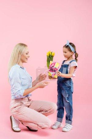 Photo pour Mère heureuse recevant des cadeaux de sa fille sur rose - image libre de droit