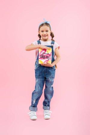 volle Länge des glücklichen Kindes hält Grußkarte mit ich liebe dich Mama Schriftzug auf rosa
