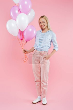 happy woman standing with hand in pocket and holding balloons on pink