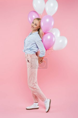 full length of cheerful woman standing and holding balloons on pink