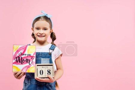 Photo pour Heureux enfant tenant carte de vœux avec je t'aime maman lettrage et cubes en bois avec 8 mars isolé sur rose - image libre de droit