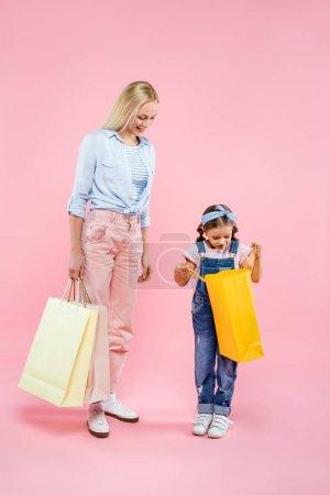 Photo pour Pleine longueur de bonne humeur mère et fille regardant sac à provisions sur rose - image libre de droit