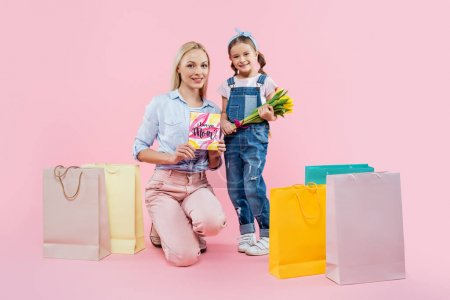 Photo pour Pleine longueur de la mère tenant la carte de vœux près de l'enfant avec des fleurs et des sacs à provisions sur rose - image libre de droit