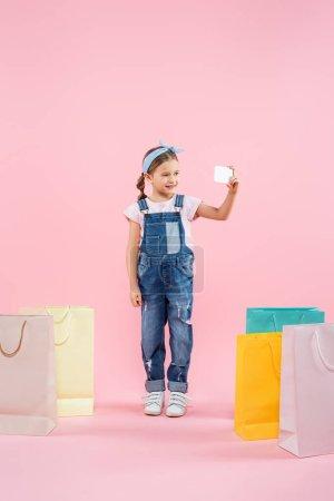 Photo pour Pleine longueur de gosse joyeux prendre selfie sur smartphone près de sacs à provisions sur rose - image libre de droit