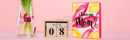 wooden calendar with 8 march lettering near greeting card and vase with flowers on pink, banner