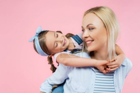 cheerful child hugging happy mother isolated on pink