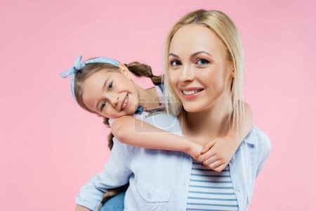 Photo for Cheerful child hugging happy mother and looking at camera isolated on pink - Royalty Free Image