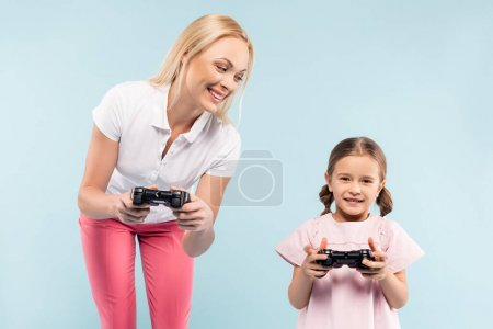 KYIV, UKRAINE - NOVEMBER 25, 2020: happy mother and daughter holding joysticks isolated on blue