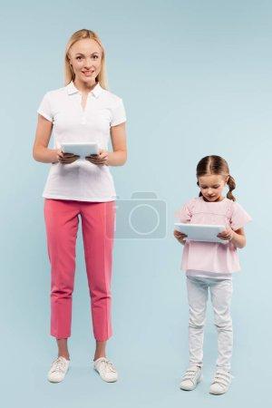 Photo pour Pleine longueur de bonne humeur mère et fille tenant des comprimés numériques sur bleu - image libre de droit