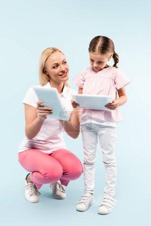 Photo pour Pleine longueur de mère et fille heureux tenant des comprimés numériques sur bleu - image libre de droit