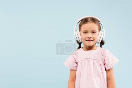 Photo pour Enfant heureux dans un casque sans fil souriant isolé sur bleu - image libre de droit