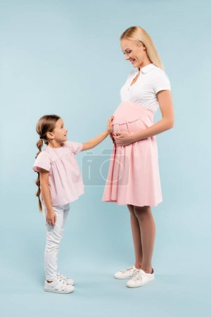 full length of daughter touching belly of pregnant mother on blue
