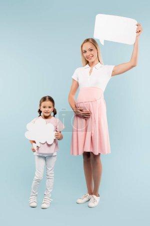 Photo pour Pleine longueur de mère enceinte et enfant heureux tenant la pensée et les bulles de la parole sur le bleu - image libre de droit