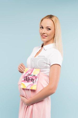 Photo pour Heureuse femme enceinte tenant carte de vœux avec je t'aime maman lettrage isolé sur bleu - image libre de droit