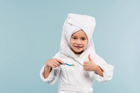 happy kid in bathrobe and towel on head holding toothbrush with toothpaste while showing thumb up isolated on blue