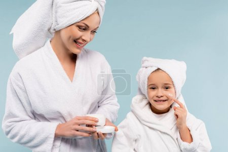 happy mother in bathrobe holding container and looking at daughter applying cosmetic cream on face isolated on blue