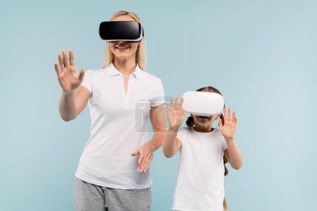 joyeuse mère et enfant dans vr casques geste isolé sur bleu