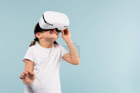 cheerful child adjusting vr headset isolated on blue