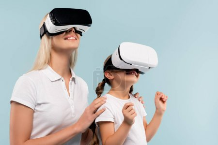 cheerful mother and happy kid in vr headsets isolated on blue