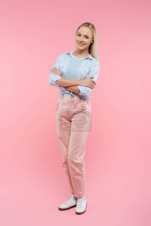 Photo for Full length of happy and blonde woman standing with crossed arms on pink - Royalty Free Image