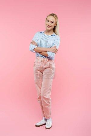longitud completa de la mujer feliz y rubia de pie con los brazos cruzados en rosa