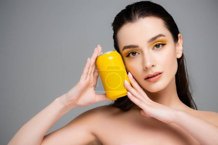 Photo for Brunette young woman holding yellow can with soft drink isolated on grey - Royalty Free Image