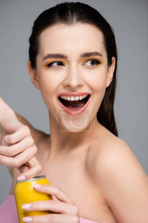 Photo for Excited young woman opening yellow can with soft drink isolated on grey - Royalty Free Image