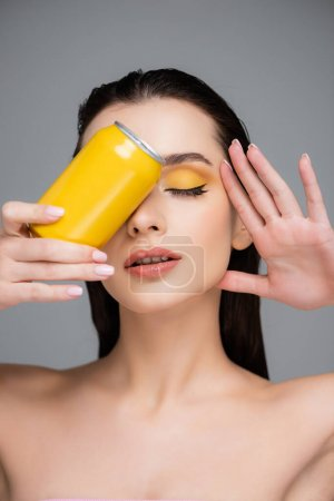 Photo pour Brunette jeune femme avec les yeux fermés tenant boîte jaune avec boisson gazeuse isolé sur gris - image libre de droit
