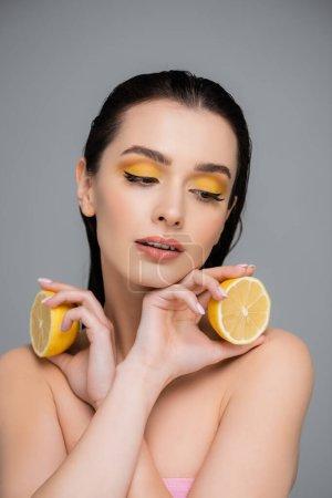 brünette Frau mit nackten Schultern, die gelbe Zitronenhälften isoliert auf grau hält