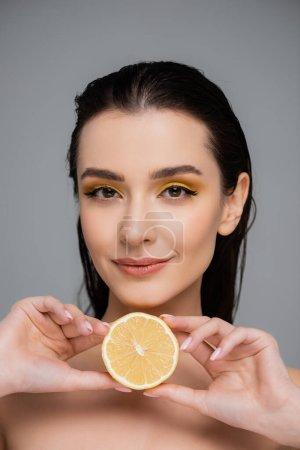 mujer joven con hombros desnudos sosteniendo la mitad de limón maduro aislado en gris