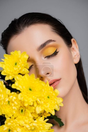 young brunette woman with makeup near blooming yellow flowers isolated on grey