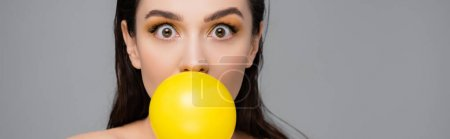 Photo for Young brunette woman with makeup blowing yellow bubblegum isolated on grey, banner - Royalty Free Image
