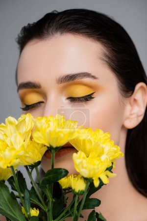 young woman with yellow eyeshadows and closed eyes covering face with flowers isolated on grey