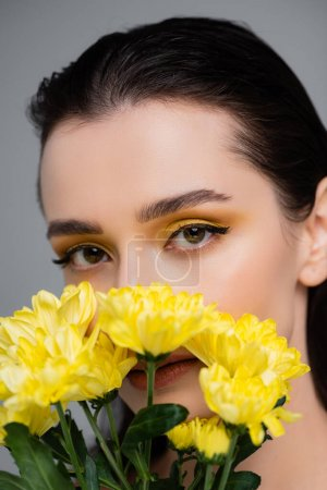 young woman with yellow eyeshadows covering face with blooming flowers isolated on grey
