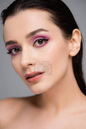 young woman with pink eye shadows and bare shoulders isolated on grey