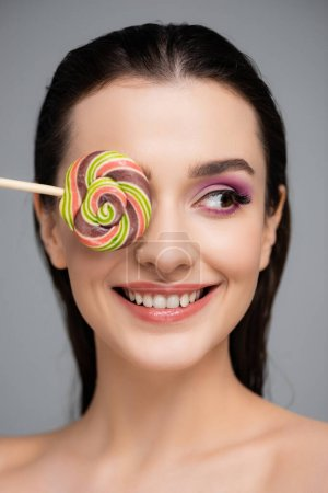 happy young woman with pink eye shadows covering eye with lollipop isolated on grey