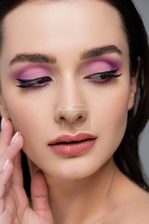 close up of brunette woman with pink eye shadows looking away isolated on grey