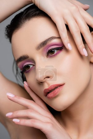 close up of brunette woman with pink eye shadows posing isolated on grey