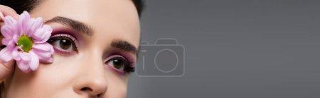vista parcial de mujer sensual con sombras de ojos rosados sosteniendo flor aislada en gris, bandera