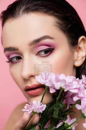 close up of young sensual woman looking away near flowers isolated on pink