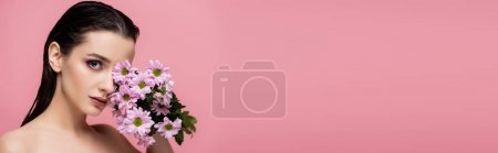 Photo for Young sensual woman holding flowers isolated on pink, banner - Royalty Free Image