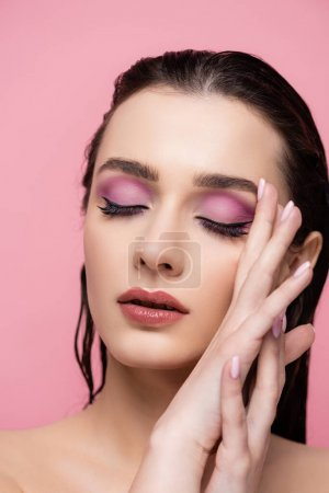 young sensual woman with makeup and closed eyes isolated on pink