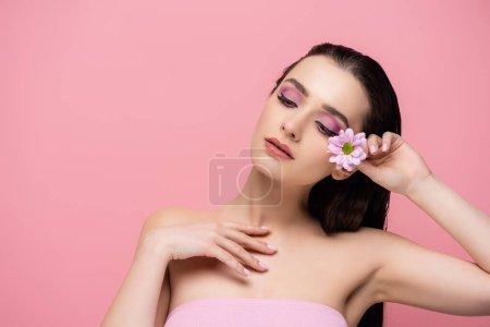 sensual mujer joven sosteniendo la flor mientras mira hacia otro lado aislado en rosa