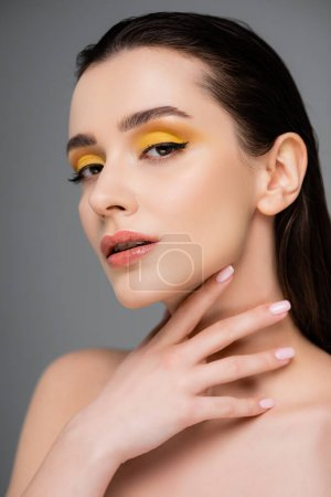 young pretty woman with yellow eyeshadow looking at camera isolated on grey