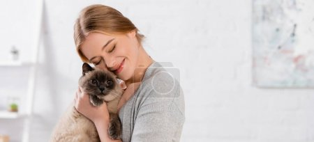 Cheerful woman with closed eyes embracing siamese cat, banner