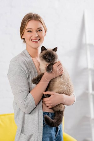 Happy woman looking at camera while holding siamese cat at home