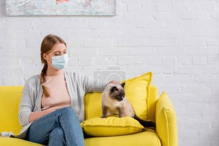 Photo pour Femme en masque médical souffrant d'allergie près du chat siamois - image libre de droit