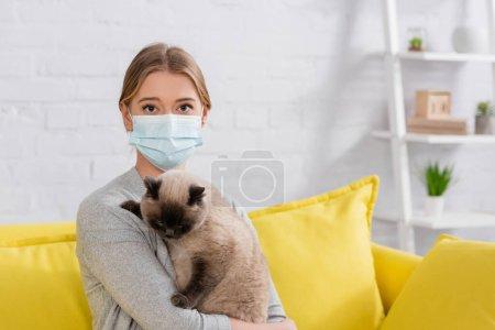 Photo pour Jeune femme en masque médical regardant la caméra tout en tenant le chat siamois - image libre de droit